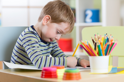 Preschool kid use pencils and paints for his homework